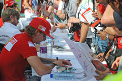 Kimi signs autographs